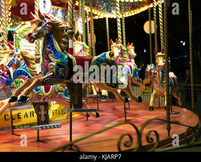 Colorful vintage carousel (merry-go-round) lit up at night on the South Bank in London, England, United Kingdom - Stock Photo