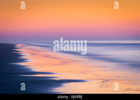 Waves In Motion As They Crash On Beach At Sunrise - Stock Photo
