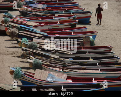 A man walking on tarrafal beach in cape verde, among colored small wooden boats aligned on the sand - Stock Photo