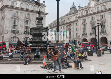 Piccadilly Circus, London-September 6,2017: Tourists sitting and listening music band on the steps of the Fountain - Stock Photo