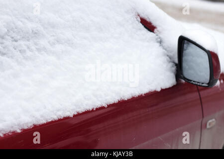 Frozen car covered snow in winter day, view front window windshield and hood on snowy background . - Stock Photo