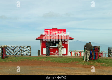 A small curio shop made from corrugated metal sheets with people standing outside, Kenya, East Africa - Stock Photo