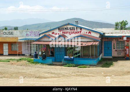 Two African men sit outside a small restaurant and other shops, Kenya, East Africa - Stock Photo