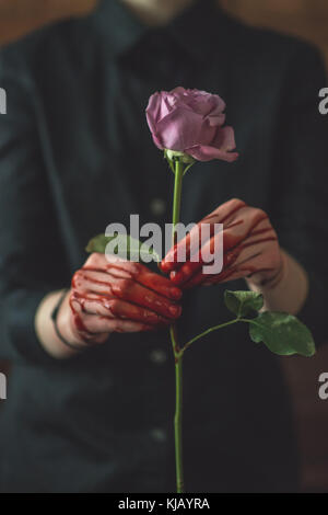 Young Women Holding A bloody Rose - Stock Photo