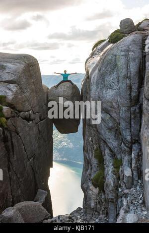 Woman on Kjeragbolten Travel in Norway - Stock Photo