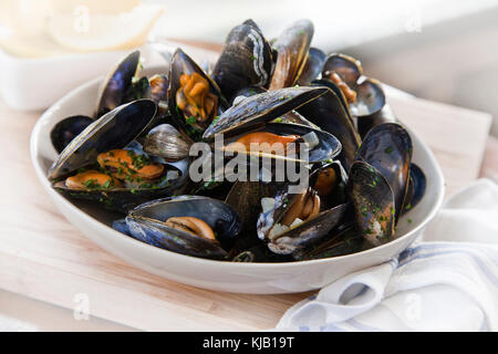 Cooked mussels in white bowl on wooden base - Stock Photo