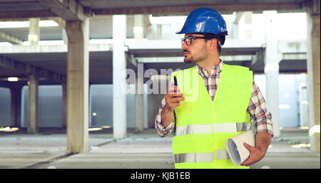 Male architect with blueprints using walkie-talkie - Stock Photo