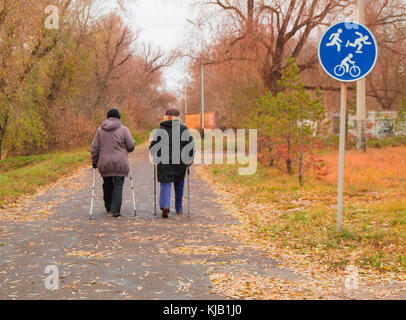 Nordic walking for two elderly women outdoors in autumn Park. - Stock Photo