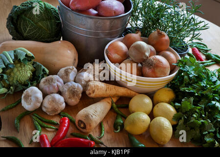 Freshly harvested vegetable and herb selection on wooden table. - Stock Photo