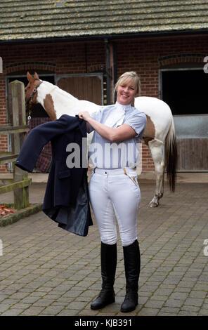 Smartly dressed horse rider putting on a dark blue riding jacket, November 2017 - Stock Photo