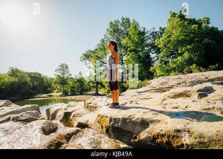 Caucasian woman standing on rocks near river - Stock Photo