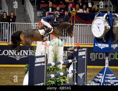 Kent Farrington on Voyeur soaring to a first place win at the Longines FEI World Cup Show Jumping competition jump - Stock Photo