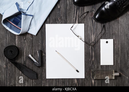 Set of businessman fashion accessories and blank paper in the middle, top view on white wooden background - Stock Photo