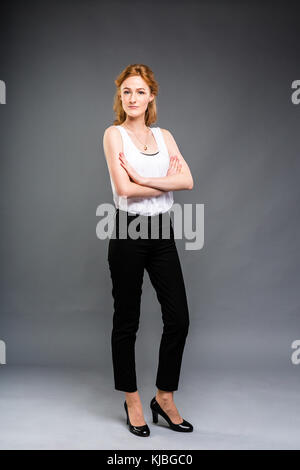 beautiful young Caucasian woman with long red hair in high heels, black trousers and a white shirt stands in full - Stock Photo
