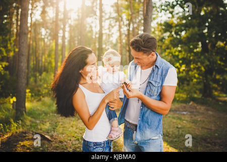 stylish young Family mom, dad and daughter one year old blonde sitting with father on shoulders playing happy and - Stock Photo