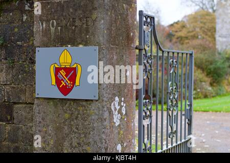 Crest of Wolvesey Castle next to open gates, Winchester, UK - Stock Photo