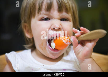 Messy child eating with a spoon - Stock Photo