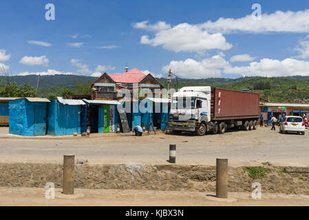 A lorry sits parked outside small metal shops off of the main road in Mau Mahiu town, Kenya, East Africa - Stock Photo