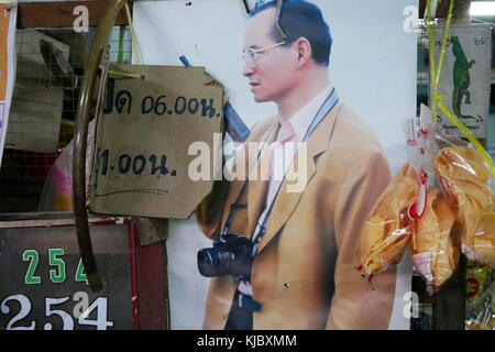 A poster of the late Thai king Bhumibol Adulyadej, known as Rama IX, with a camera around his neck, in a market - Stock Photo