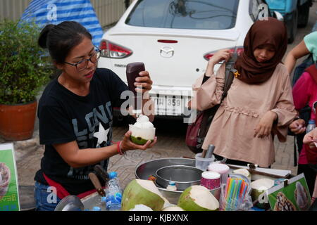 A woman is waiting for her food at a street vendor coconut ice cream stall in Bangkok, Thailand. - Stock Photo