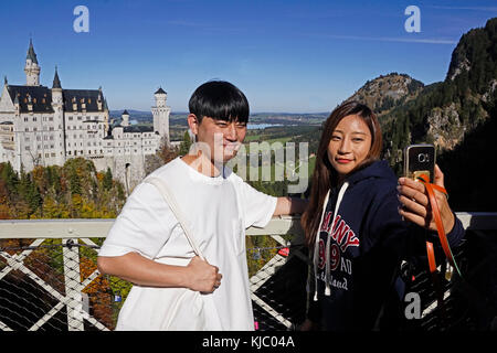 Young Chinese tourist couple doing a selfie at Neuschwanstein Castle in Bavaria, Germany. - Stock Photo