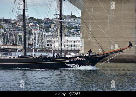 Black sailing scow Spirit of New Zealand cruising under Harbour Bridge in Auckland. - Stock Photo