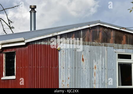 Shed made from partially rusty corrugated sheet metal panels. - Stock Photo