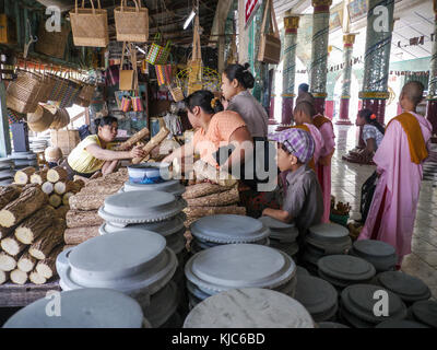 Inside Kaunghmudaw Paya Burmese women and Burmese Buddhist nuns buy wood bark to make natural thanaka from a woman - Stock Photo