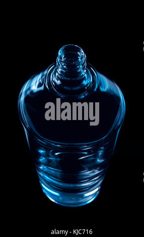 Perfumery glass bottle. Blue color on black background - Stock Photo