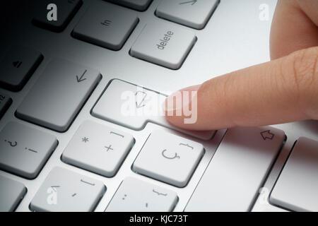 Index finger pressing enter key at keyboard. Fade light effect on keyboard. Enter concept. - Stock Photo