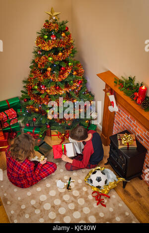 Overhead view of Children opening their gift wrapped presents on Christmas morning sitting next to the tree and - Stock Photo