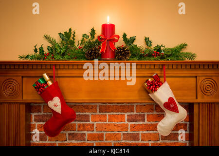 Two Christmas stockings with gift wrapped presents hanging on a mantelpiece over a fireplace, plus burning candle - Stock Photo