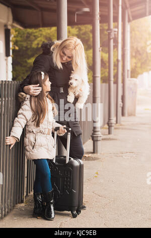 Mother, daughter and their dog  on a railway station. Kid and woman waiting for train and happy about a journey. - Stock Photo