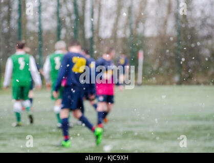 GLASGOW, SCOTLAND - FEBRUARY 13 2016: A football match being played in the snow in Glasgow, Scotland. - Stock Photo