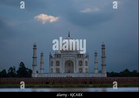 Taj Mahal under storm clouds as seen from Mehtob Bagh Park across the Yamuna River in Agra, India. - Stock Photo