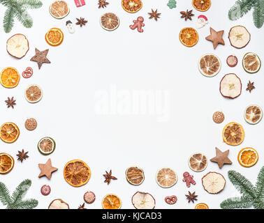Christmas frame made with fir branches and dried fruits , spices and holiday candies on white desk background. Creative - Stock Photo