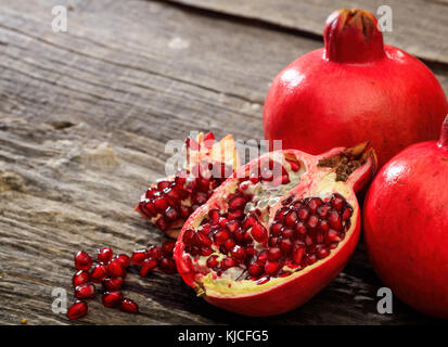 Pomegranates on a wooden table, copy space - Stock Photo