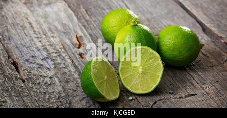 Cut and whole limes on wooden table, copy space - Stock Photo