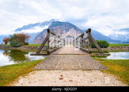 Idyllic scenery with a rustic old bridge on the Hallstatter lake, at the end of which lay the Dachstein mountains, - Stock Photo