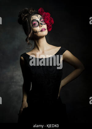 Beautiful Mexican American woman celebrating Día de los Muertos ( Día de Muertos ) is the Mexican holiday also known as Day of the Dead with skull makeup and roses in the style of Catrina.