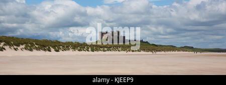 Bamburgh Castle Northumberland England UK with white sandy beach panoramic view - Stock Photo