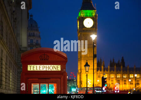 Red London telephone box with Big Ben at night - London, UK - Stock Photo