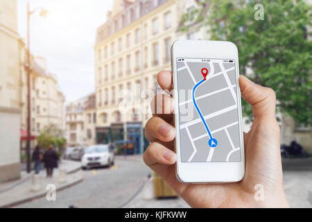 Tourist using GPS map navigation app on smartphone screen to get direction to destination address in the city streets, - Stock Photo