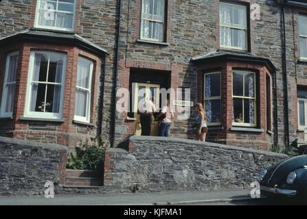 Family of bicyclists on a trip preparing to enter a youth hostel with a sign reading Cherryvale, 1965. - Stock Photo