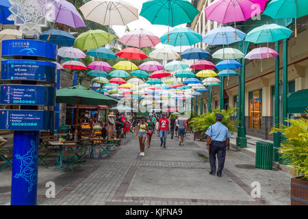 Colourful umbrellas hanging over the shopping mall Caudan Waterfront in Port Louis, Mauritius, Africa. - Stock Photo