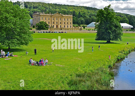 Families relaxing and enjoying a sunny day's picnic by the river in the grounds of Chatsworth House. A marquee in - Stock Photo