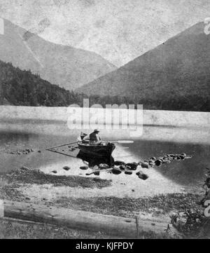 Photograph of a man in a canoe, in shallow water, mountains in the background, titled 'Echo Lake and Franconia Notch, - Stock Photo