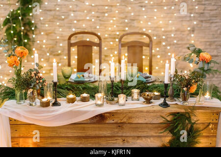 romance, comfort, holidays concept. romantic table setting for two lovers with numerous of the candles in various - Stock Photo