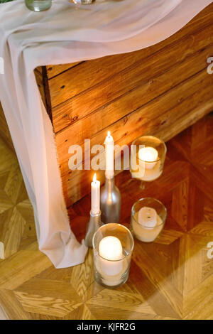 illumination, atmosphere, feast concept. few burning candles in original holders are standing on the floor nearby - Stock Photo