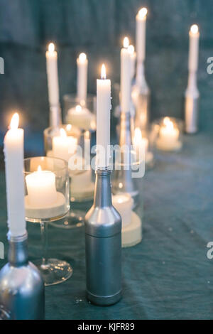 romance, winter, interior concept. in the light of sparkling fires of candle holders that covered by silver paint, - Stock Photo